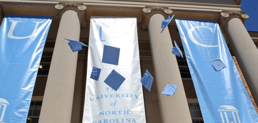 Students throw their caps in the air for a photo session in front of South Building on the campus of the University of North Carolina at Chapel Hill. The university will hold commencement exercises Sunday, May 12.